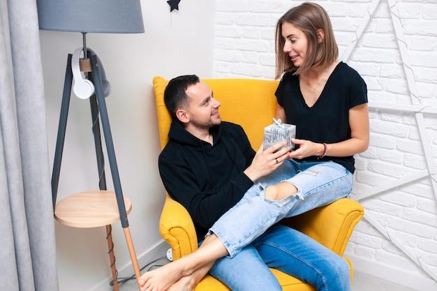 Paar jung sitzen im gelben stuhl mit geschenk
