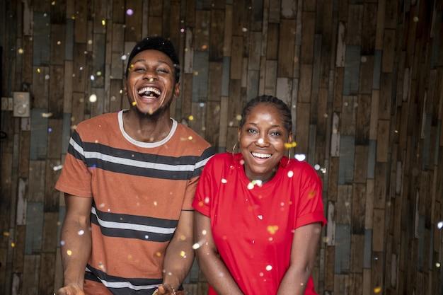 Paar junge afrikanische männer und frauen, die mit herumschwebenden konfetti feiern
