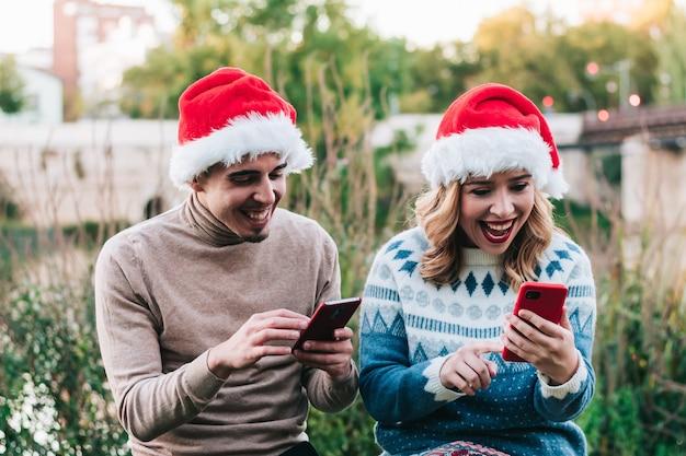 Paar junge erwachsene freunde, zu weihnachten mit handy mit weihnachtsmützen. video-chat und online-weihnachtsshopping.