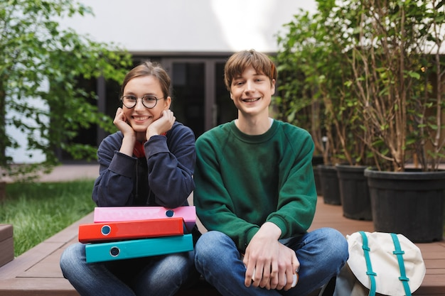 Paar junge lächelnde studenten, die mit bunten ordnern und glücklich sitzen