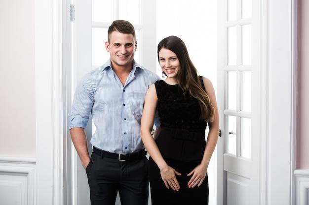 Paar junge stilvolle geschäftsleute in der tür nach hause innen loft büro