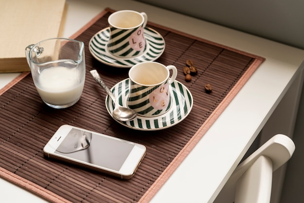 Paar kaffeetassen mit einem smartphone auf dem tisch