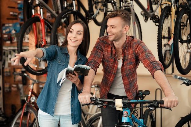 Paar kam zum fahrradladen, um ein neues fahrrad zu wählen.