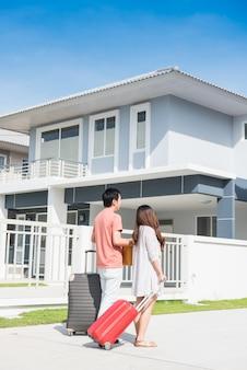 Paar kauft ein neues zuhause. umzug von gerät und kleidung ins haus.