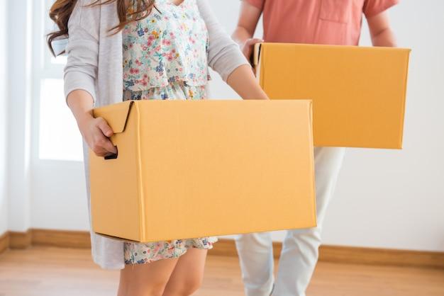 Paar kauft ein neues zuhause. umzugskarton ins haus.
