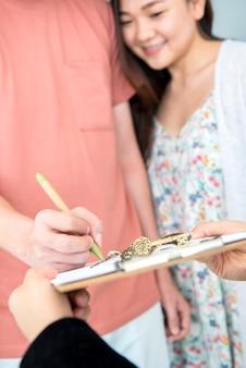 Paar kauft ein neues zuhause. unterschreiben sie kontakt und erhalten sie einen schlüssel.
