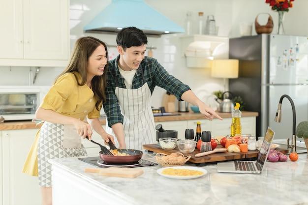 Paar kochen frühstück indem sie sich ansehen, wie man einen laptop macht