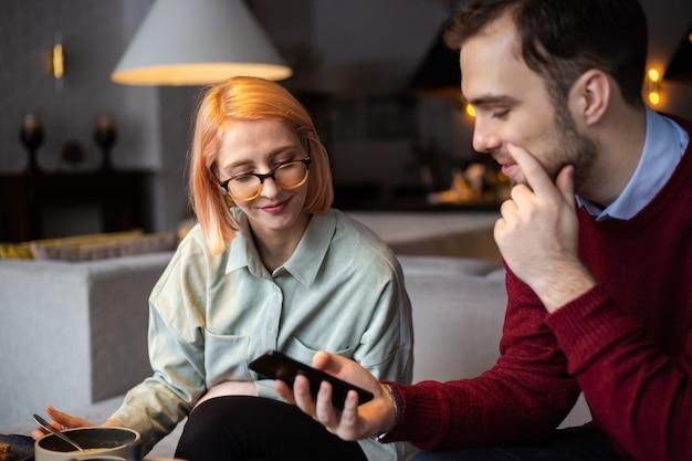 Paar kommuniziert im café und schaut in das smartphone, trinkt tee im café