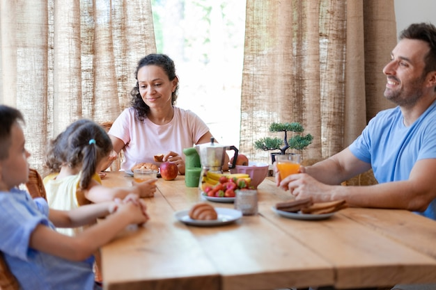 Paar kommuniziert während des frühstücks mit seinen kindern und bespricht pläne für diesen sonnigen tag