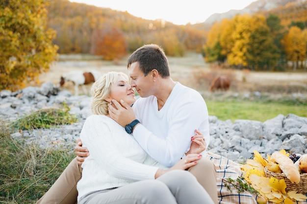 Paar küsst sich beim sitzen auf einer decke gegen pferde, die im herbst grasen