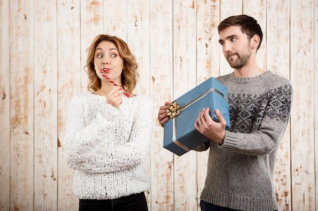 Paar lächelnd, das weihnachtsbonbon und geschenk über holzwand hält