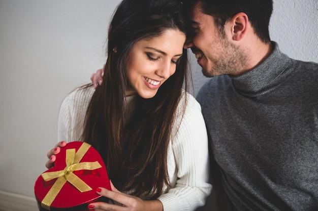 Paar lächelnd und sie mit einem geschenk in den händen