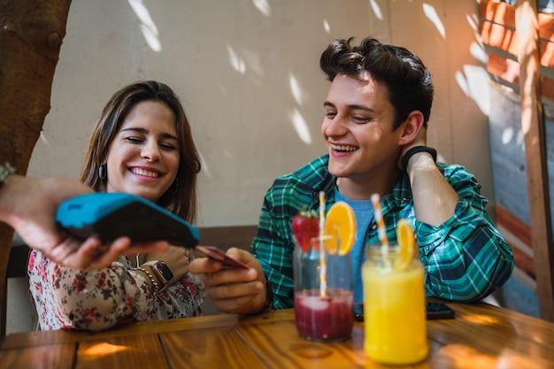 Paar lächelt in einer bar, während der junge mann die rechnung mit einer kreditkarte bezahlt.
