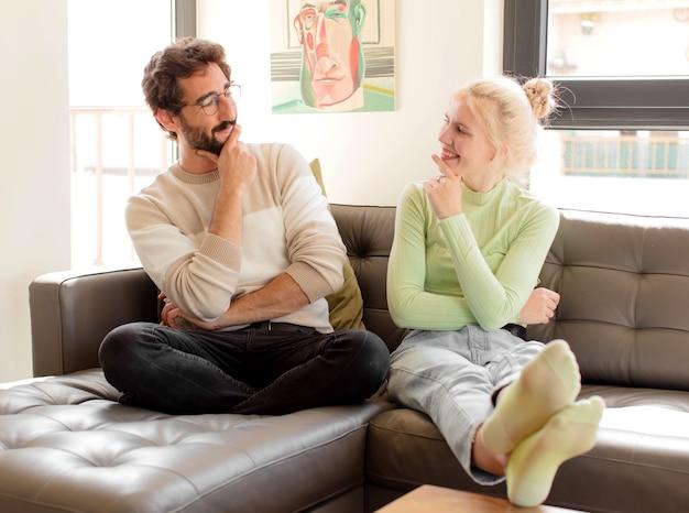 Paar lächelt mit einem glücklichen, selbstbewussten ausdruck mit der hand am kinn, wundert sich und frau, die zur seite schaut