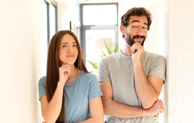 Paar lächelt mit einem glücklichen, selbstbewussten ausdruck mit der hand am kinn, wundert sich und schaut zur seite