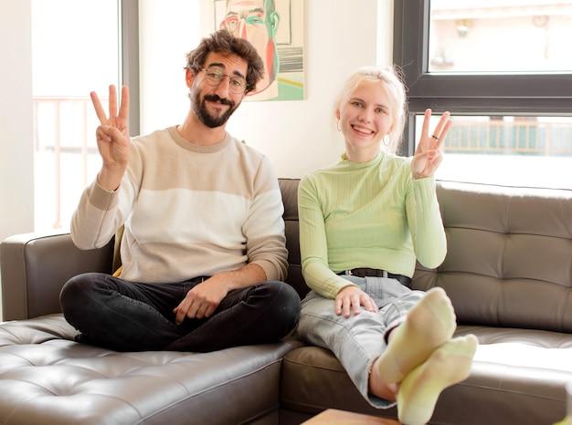 Paar lächelt und sieht freundlich aus, zeigt nummer drei oder drei mit der hand nach vorne und zählt herunter