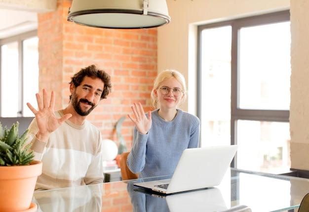 Paar lächelt und sieht freundlich aus, zeigt nummer fünf oder fünf mit der hand nach vorne und zählt herunter