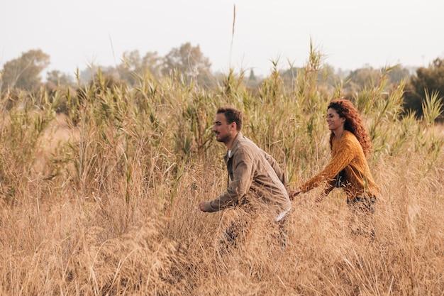 Paar läuft durch weizenfeld