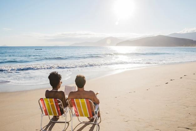 Paar lesung auf liegestühlen am strand