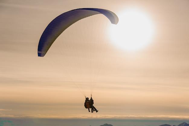 Paar leute, die auf einem fallschirm mit großem leuchtendem himmel fliegen