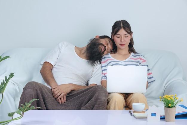 Paar liebe arbeiten zusammen, während alter mann in der nähe von jungem mädchen auf dem sofa zu hause nickerchen macht.