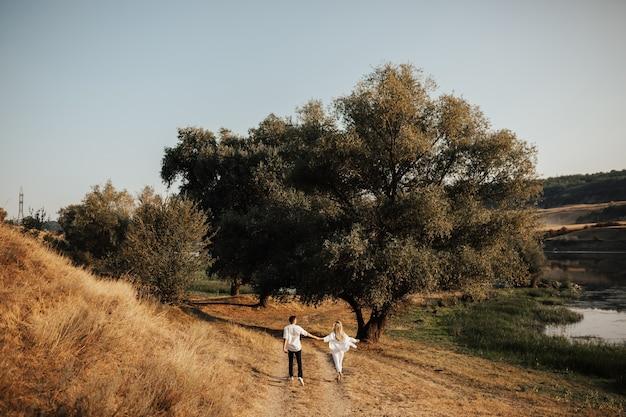 Paar liebhaber, die hände halten und laufen und spaß im park haben. frau und mann im freien verliebt.