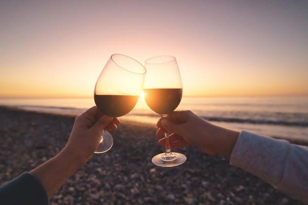 Paar liebhaber, die rotwein trinken, während sie sonnenuntergang beobachten und seeurlaub bei flitterwochen genießen
