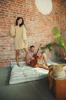 Paar liebhaber zu hause, die zusammen entspannen. kaukasischer mann, der gitarre spielt, während frau tanzt. wochenende zu haben, sieht zart und glücklich aus. konzept der beziehungen, familie, herbst und winter komfort.