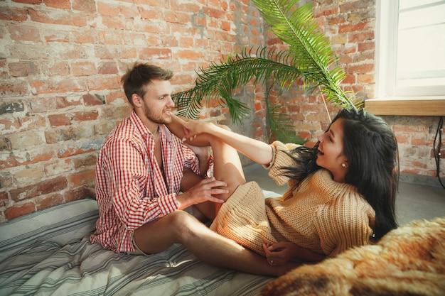 Paar liebhaber zu hause, die zusammen entspannen. kaukasischer mann und frau, die wochenende haben, sehen zart und glücklich aus