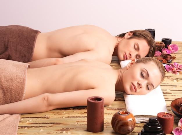 Paar liegt auf den massageschaltern im spa-salon. schönheitsbehandlungskonzept.