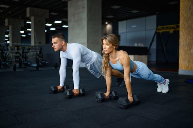 Paar macht liegestütze mit hanteln im fitnessstudio