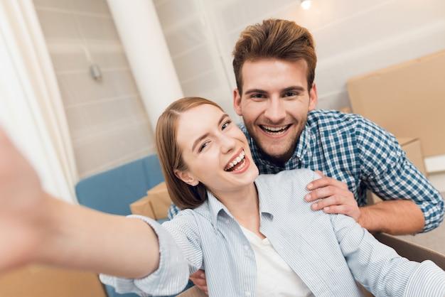Paar macht selfie beim umzug in neue wohnung.