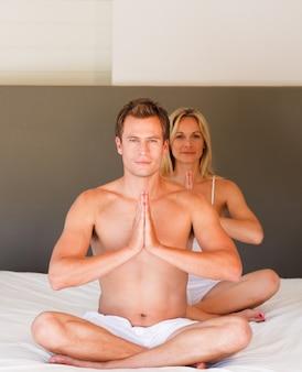 Paar macht übungen auf dem bett