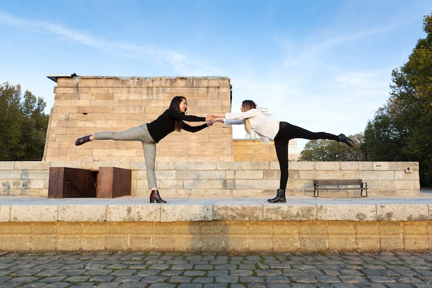 Paar mädchen, die zusammen yoga-stellungen in der stadt üben. platz für text.