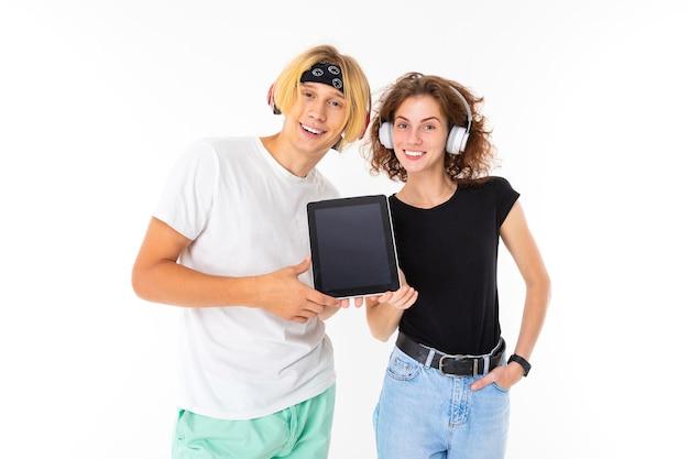 Paar mädchen und ein junger mann in kopfhörern halten eine tablette mit einem modell auf einem weißen hintergrund.