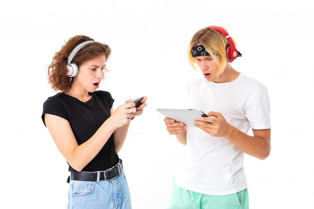 Paar mädchen und kerl spielen auf tablet und telefon an einer weißen wand