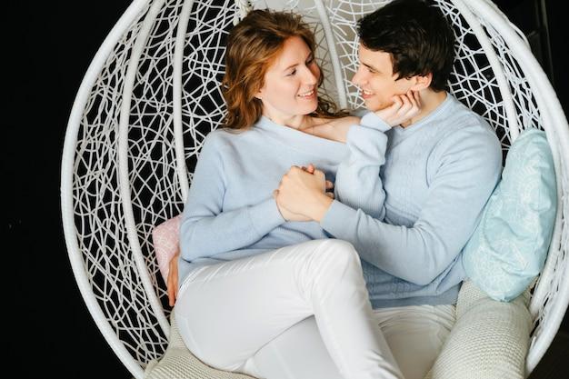 Paar mädchen und kerl umarmen auf einem großen stuhl. weißer und blauer pullover.