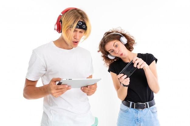 Paar mädchen und mann in kopfhörern schauen filme auf einem tablet und telefon auf einer weißen wand