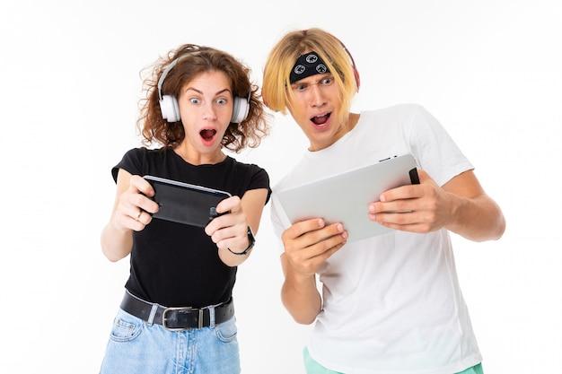 Paar mädchen und mann in kopfhörern spielen spiele auf einem tablet und telefon auf einer weißen wand