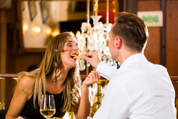Paar, mann und frau ein gutes restaurant, sie essen fast food und pommes