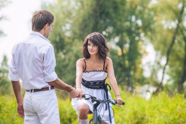 Paar mann und frau im hochzeitsstil mit fahrrädern in der natur glücklich