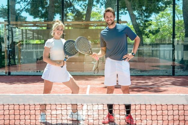 Paar mann und frau lächelt nach dem spiel auf einem tennisplatz im freien