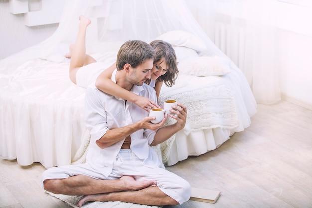 Paar mann und frau zu hause im bett mit einer tasse kaffee. zarte liebe in familiären beziehungen