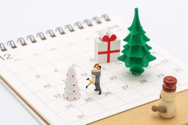 Paar-miniatur 2 leute, die auf weihnachtsbaum stehen feiern sie weihnachten