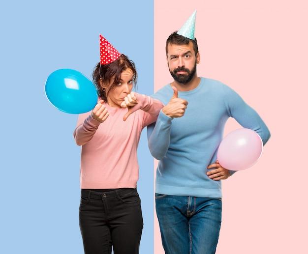 Paar mit ballons und geburtstag hüte machen gut-schlechtes zeichen