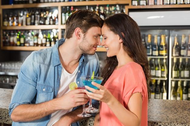 Paar mit cocktails anstoßen