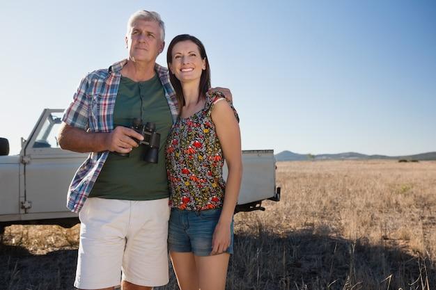Paar mit dem fahrzeug auf landschaft