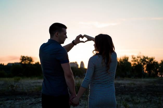 Paar mit der schwangeren frau, die hände hält und eine herzform auf bauch bei sonnenuntergang macht