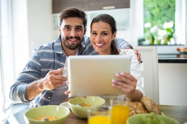 Paar mit digitalem tablet beim frühstück zu hause