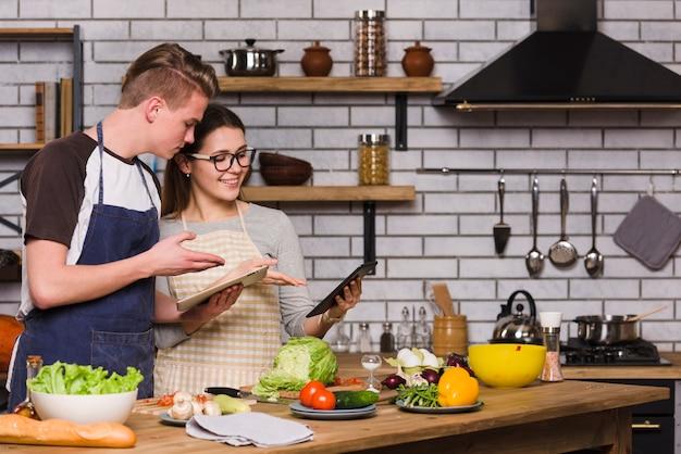 Paar mit digitalen tabletten bei der zubereitung von speisen